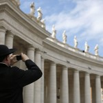 A priest stands near the colonnade as he takes a photo of Saint Peter's Basilica with his camera at the Vatican