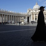 A priest walks through Saint Peter's Square at the Vatican