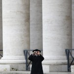 A priest stands near the colonnade as he takes pictures at Saint Peter's Basilica