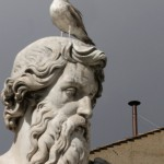A seagull perches on St Paul's statue in front of the chimney set on the roof of the Sistine Chapel at the Vatican