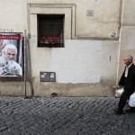 A man walks past a portrait of former Pope Benedict XVI at a street near Saint Peter's Square