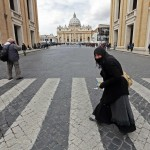 A woman crosses the street in front of Saint Peter's Square