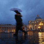 People walk through Saint Peter's Square at the Vatican