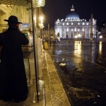 A priest makes a phone call from a phone box outside the Vatican in Rome