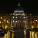 Saint Peter's Basilica is illuminated as seen from a rain soaked street in Rome