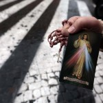 A faithful offers a religious leaflet depicting the Christ at the Vatican