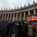People in Saint Peter's Square shelter from rain as they watch a live television screen showing cardinals entering the Sistine Chapel at the Vatican