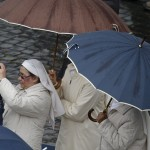 Nuns hold umbrellas in Saint Peter's Square during the second day of voting for the election of a new pope, at the Vatican