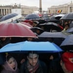 A crowd forms under umbrellas to wait for the sight of smoke from the chimney on top of the Sistine Chapel, during the second day of voting for the election of a new pope at the Vatican