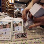 The first batch of freshly-printed pictures of the newly-elected Pope Francis are displayed for customers at a souvenir shop at the Vatican