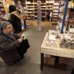 A nun takes a photograph of the first batch of souvenirs adorned with freshly-printed pictures of the newly-elected Pope Francis in a shop at the Vatican