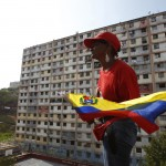 A woman holds the national flag while standing on the roof of a building during the funeral parade of Venezuela's late President Hugo Chavez in Caracas