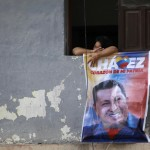 A woman cries while holding onto a poster of Venezuela's late President Hugo Chavez during his funeral parade in Caracas