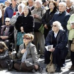 People watch a live televised broadcast showing Pope Francis celebrating his inaugural mass in Saint Peter Square at the Vatican