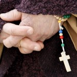 A faithful holds a rosary while Pope Francis celebrates his inaugural mass in Saint Peter Square at the Vatican