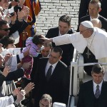 Pope Francis leans out to touch a child's head as he arrives in Saint Peter's Square for his inaugural mass at the Vatican
