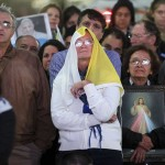 A woman is covered with a Vatican flag as she and other faithful watch a televised broadcast of the inaugural mass of Pope Francis near the Metropolitan Cathedral in Buenos Aires