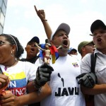 Opposition supporters hold a crucifix as they take part in protest in Caracas