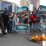 Supporters of the late President Hugo Chavez burn a students' flag during a protest in Caracas