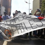 Supporters of the late President Hugo Chavez burn a banner during a protest in Caracas