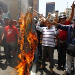 Supporters of the late President Hugo Chavez burn a flag with Capriles' campaign logo during a protest in Caracas