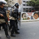 Riot police take cover behind shields as they break up a demonstration in Caracas