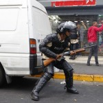 Riot police officer takes cover behind a car as he attempts to break up a demonstration in Caracas