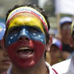 An opposition supporter with his face painted with colours of the national flag takes part in protest in Caracas