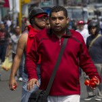 A supporter of Venezuela's late President Chavez holds tomatoes as he takes part in a protest in Caracas