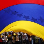 Opposition supporters hold a large national flag as they take part in a protest in Caracas