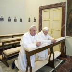 Pope Francis prays with Pope Emeritus Benedict XVI after arriving at the Castel Gandolfo summer residence, south of Rome