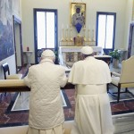 Pope Francis prays with Pope Emeritus Benedict XVI after arriving at the Castel Gandolfo summer residence