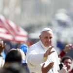 Pope Francis waves as he arrives to lead the weekly general audience in Saint Peter's Square at the Vatican