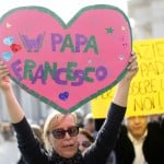 A faithful holds a sign during the weekly general audience in Saint Peter's Square at the Vatican