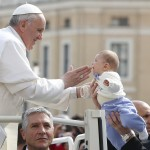 Pope Francis blesses a baby as he arrives to lead the weekly general audience in Saint Peter's Square at the Vatican