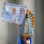 A faithful holds a portrait of Pope Francis during the weekly general audience in Saint Peter's Square at the Vatican