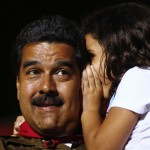 Venezuela'spresidential candidate Nicolas Maduro talks with his granddaughter during a campaign rally in Caracas