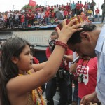 An indigenous girl gives a feather headgear to Venezuela's acting President and presidential candidate Nicolas Maduro during a campaign rally at the state of Amazonas