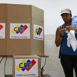 A Venezuelan woman folds up her marked ballot before depositing it in a box during the election in Caracas