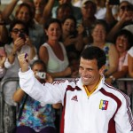 Venezuelan opposition leader and presidential candidate Capriles holds up his ink-stained finger after casting his ballot for the successor to late President Chavez, in Caracas