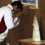 Venezuelan opposition leader and presidential candidate Capriles holds his marked ballot in his left hand as he stops to pray at a statue of the Virgin in Caracas