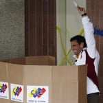 Venezuelan opposition candidate Capriles holds up his marked ballot inside a voting booth, as he votes for the successor to late President Chavez, in Caracas