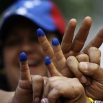 Venezuelans living in Mexico pose with their ink-stained fingers after voting for a successor to the late President Chavez, outside their embassy in Mexico City