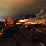 A vehicle is seen near the remains of a fertilizer plant burning after an explosion at the plant in the town of West, near Waco, Texas