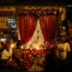 "A family surrounds an altar outside their home to wait for the ""Diablos Danzantes"" of Yare during the Feast of Corpus Christi in San Francisco de Yare"