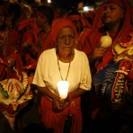 "Woman holds a candle as she stands among ""Diablos Danzantes"" of Yare during the Feast of Corpus Christi in San Francisco de Yare"