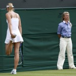 Maria Sharapova of Russia stretches after slipping during her women's singles tennis match against Michelle Larcher De Brito of Portugal at the Wimbledon Tennis Championships, in London
