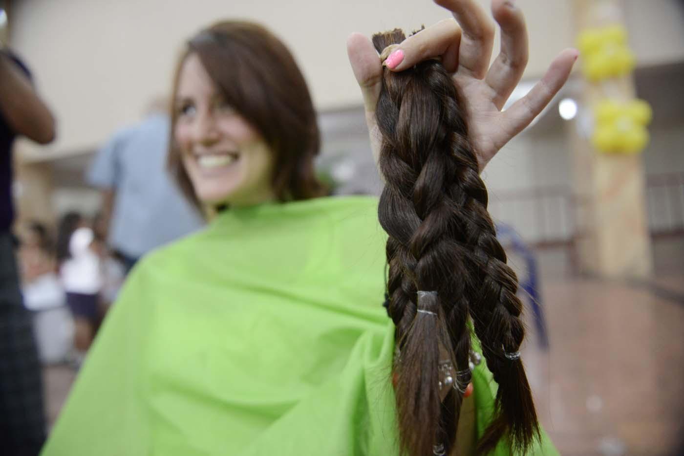 Una donadora de cabello muestra con felicidad su apoyo
