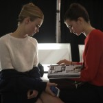 Models read backstage before the presentation of the Carolina Herrera Spring/Summer 2014 collection during New York Fashion Week