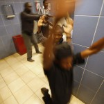 Armed police search customers inside a bathroom while combing through a shopping centre for gunmen in Nairobi